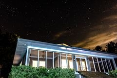 Illuminated screened porch against night sky. House with a screened in porch illuminated against the night sky with wispy clouds and stars Royalty Free Stock Photo