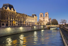 Illuminated Seine river and Notre-Dame cathedral early in the ev Royalty Free Stock Photography