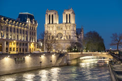Illuminated Seine river and Notre-Dame cathedral at night Stock Image