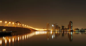 Illuminated Shaikh Khalifa bridge and Jufffair skyline with reflection, Bahrain Stock Photography