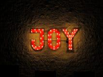 Illuminated sign Joy. An illuminated red sign with the word JOY fixed outside on a brick wall Stock Photo
