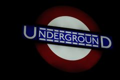 Illuminated sign of the London Underground. Logo of the London Underground on an illuminated sign against a black background Stock Photos