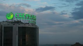 Illuminated signboard of Sberbank on background of cloudy evening sky. Russia, Novosibirsk city. Sberbank is one of biggest banks in Russia stock footage