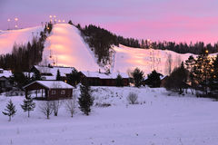 Illuminated ski slopes, Finland. Ski slopes, just after sunset, are lit with artificial light to enable skiers to continue their activities in the evening Stock Image