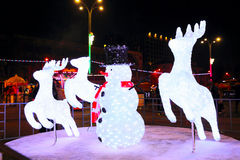Illuminated snowman with christmas deers Stock Photo