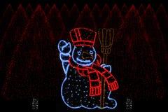 Illuminated Snowman and christmas trees Stock Photo