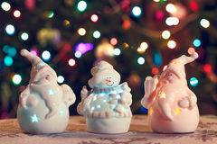 Illuminated Snowman and Jack Frost (Santa Claus) dolls in front of Christmas tree lights, blurred background Stock Photo
