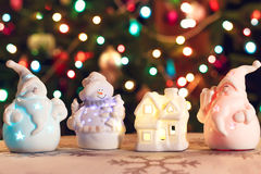 Illuminated Snowman and Jack Frost (Santa Claus) dolls in front of Christmas tree lights, blurred background Royalty Free Stock Photos