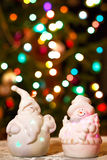 Illuminated Snowman and Jack Frost (Santa Claus) dolls in front of Christmas tree lights, blurred background Royalty Free Stock Images