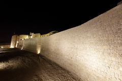 Illuminated Southern wall with moat of Bahrain Fort Stock Images