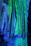 Illuminated stalactites. Colorful illuminated stalactites in the Reed flute cave, Guilin, China stock photo
