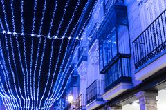 Illuminated street with blue Christmas illumination. Illuminated street with blue Christmas illumination, which is reflected in a balcony that has crystals royalty free stock images