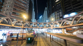 Illuminated street of Hong Kong with rails and pedestrian bridge Royalty Free Stock Photography