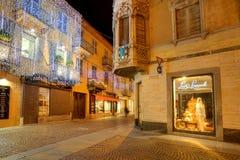 Illuminated street at night. Alba, Italy. Royalty Free Stock Image