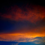 Illuminated by  sun clouds at sunset on a background of blue Royalty Free Stock Images