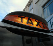 Illuminated taxi sign. Illuminated 'for hire' orange coloured taxi sign Royalty Free Stock Photos