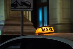 Illuminated taxi sign on the roof of a taxi at night city. Taxi sign on the roof of a taxi at night city stock image