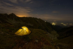 An illuminated tent above a valley. An illuminated tent in the night mounted above a valley in mountain and many villages lit Stock Photography