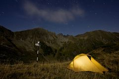 An illuminated tent at night next to a pole with a. Rrows in a wild mountain scenery and the sky full of stars Royalty Free Stock Images