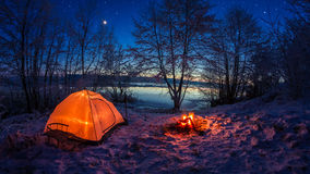 Illuminated tent in the winter camp by the lake at night with stars Stock Photos