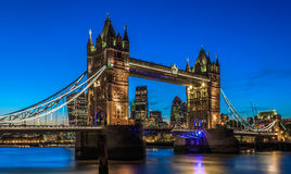 Illuminated Tower Bridge in London After Sunset. With London's financial district at the background Stock Photo