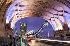 The illuminated Tower bridge with a passing by red double decker bus stock photo