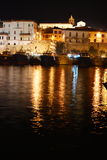 Illuminated town buildings. Whitewashed waterside buildings beside boats moored in a harbour stock photos