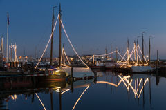 Illuminated traditional wooden fishing ships at night in Dutch harbor Royalty Free Stock Image