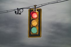 Traffic signal during a storm. Illuminated traffic lights, with a camera, underneath a stormy sky Stock Images
