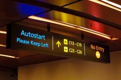 Illuminated travelator and directional signs Stock Photo