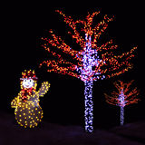 Illuminated trees and Snowman Stock Images