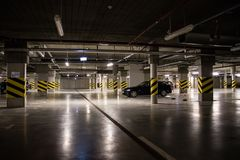 Illuminated underground car park, parking spaces in the car park. Lamp light Royalty Free Stock Photography