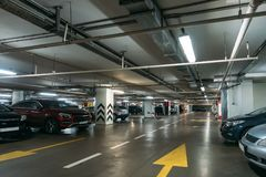 Illuminated underground car parking interior under modern mall with lots of vehicles and arrows on floor stock photography