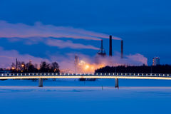 Winter morning lights. Illuminated walk bridge and factory lights on a winter morning before dawn in Oulu, Finland Stock Images