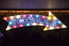 Thrills written on an illuminated arrow sign. Illuminated wall mounted arrow sign with the word Thrils written on it stock images