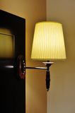 Illuminated wall-mounted lamp against orange wall Royalty Free Stock Photography