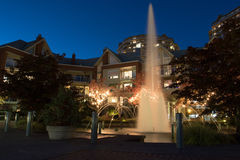 Illuminated water fountain surrounded by low rise apartment buildings. Long exposure Stock Images