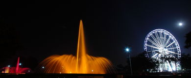 Illuminated wheel and Fountain at night Stock Photo
