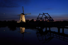 Illuminated windmill and a drawbridge at sunset Stock Image
