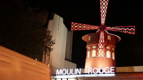 Illuminated windmill over Moulin Rouge in Paris stock video