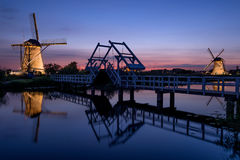 Illuminated windmills, a bridge and a canal at sunset Stock Images