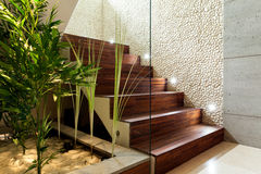 Illuminated wooden staircase. In modern house, horizontal Royalty Free Stock Photo