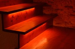 Illuminated wooden stairs. Red illuminated wooden stairs interior detail Stock Images
