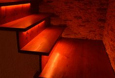 Illuminated wooden stairs. Red illuminated wooden stairs and stone wall Stock Photo