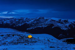Illuminated yellow tent in a wintry blue cold landscape Stock Photography