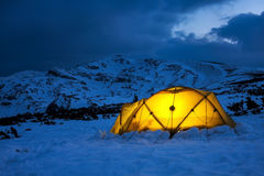 Illuminated yellow tent in a wintry blue landscape Stock Photo