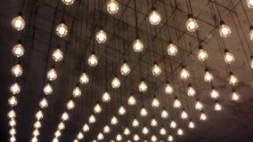 Illumination d'un grand choix d'ampoules incandescentes qui accrochent sur le plafond et vont au defocus clips vidéos