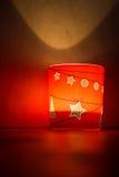 Illuminazione di vetro della candela di Natale rosso sulla tavola fotografie stock
