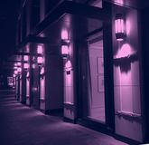 Illuminazione viola di notte della facciata moderna della costruzione della città immagini stock libere da diritti