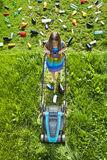 Illusion of progress and development. Young girl cutting grass and leaving plastic litter behind royalty free stock photography